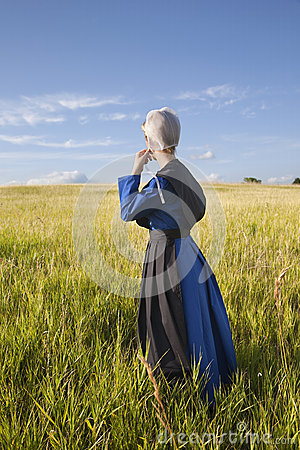 Free Amish Woman Standing In Grassy Field With Afternoon Sunlight Stock Photos - 41275473
