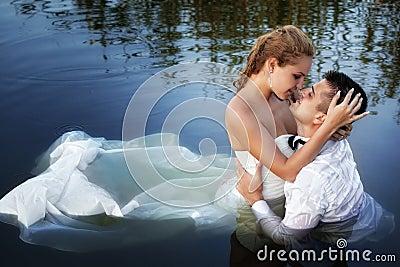 Amore e passione - bacio della coppia sposata in acqua
