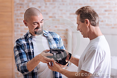 Amused friends holding the virtual reality glasses Stock Photo