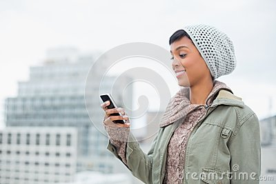 Amused young model in winter clothes looking at her mobile phone