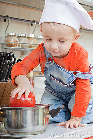 Amusing kid in a cook cap