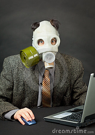 Amusing person in gas mask works with computer