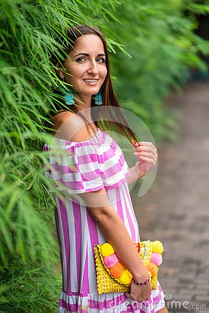 Free An Attractive Woman In A Striped Dress And A Handbag In Her Hands Leaned Against A Green Fence Stock Photography - 142974722