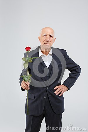 Free An Old Mature Man, In One Hand Holds Red Rose, And The Second Hand On The Belt. Royalty Free Stock Images - 105099089