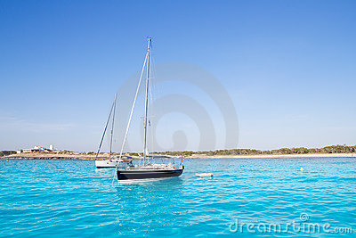 Anchored sailboats in turquoise Formentera beach