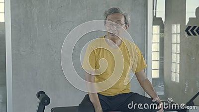Anciano asiático cansado después de hacer ejercicio en el gimnasio, masía veterano de sudor sentado expresión agotado y respirar  almacen de video