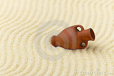 Ancient clay amphora on surface of yellow sand