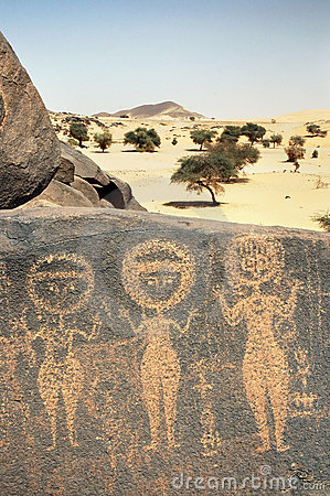 Ancient rock art in Sahara depicting three figures