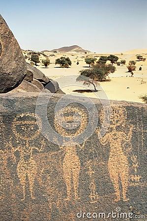 Ancient rock art in Sahara depicting three figures