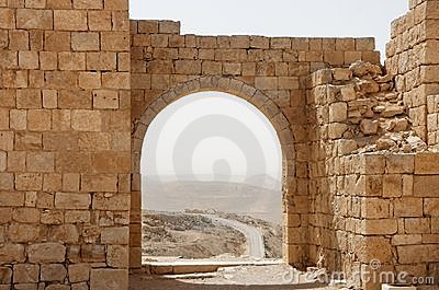 Ancient stone arch and wall with desert view durin