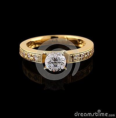 Anel de ouro com o brilhante no preto