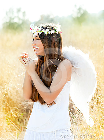 Angel girl in golden field with white wings