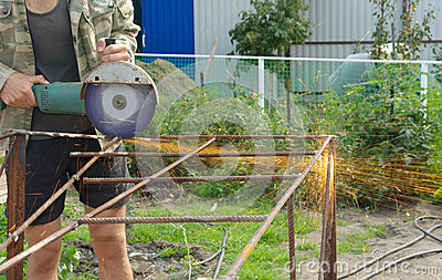 Angle Grinder Metal sawing with flashing sparks close up