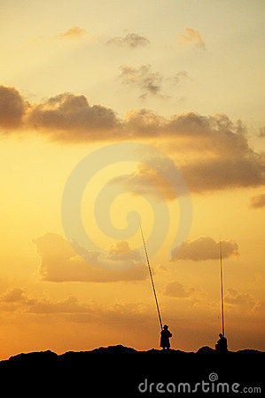 Anglers silhouetted at sunset