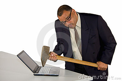 Angry businessman hitting laptop with sledgehammer