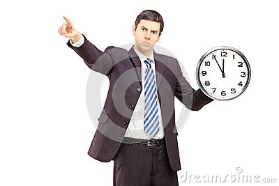 Angry businessman holding a clock and pointing with a finger