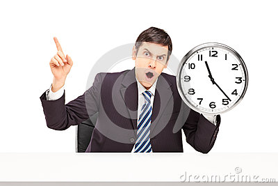 Angry businessman sitting and holding a wall clock