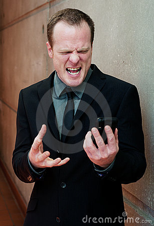 Angry businessman, yelling at cell phone
