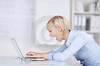 Angry Businesswoman Using Laptop While Screaming At Des