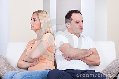 Angry couple sitting on sofa Stock Photo