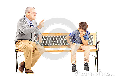 Angry grandfather shouting at his sad nephew, seated on a bench