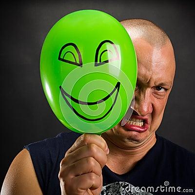 Angry man hiding behind happy balloon