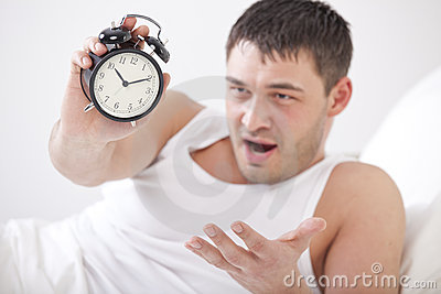 Angry man holding alarm clock