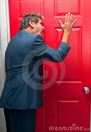 Angry man knocking on red door