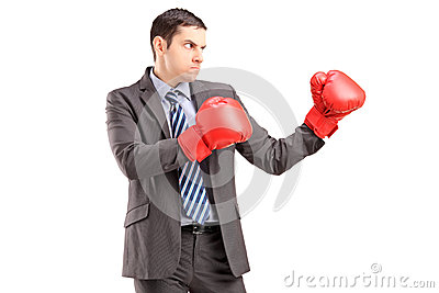 Angry man in suit with red boxing gloves ready to fight