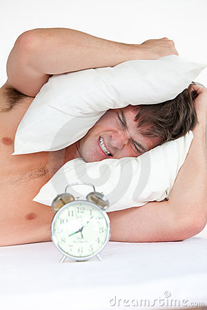 Angry man waking up by his alarm clock