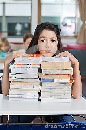 Angry Schoolgirl Resting Chin On Books