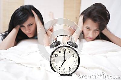 Angry sleeping women looking at a ringing clock