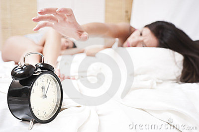 Angry sleeping women stopping a ringing clock