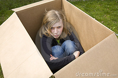 Angry teenage girl sitting in a cardboard box