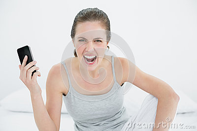 Angry woman shouting with mobile phone in hand on bed