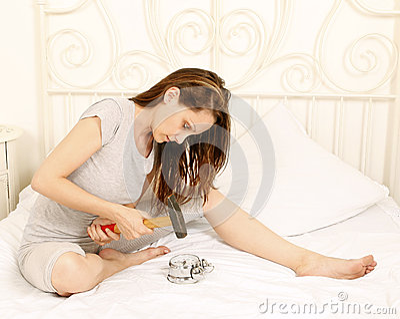 Angry woman smashing alarm clock