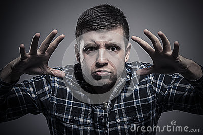 Angry young man in checked shirt threatening us with hands and frightening gaze