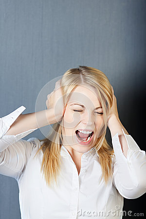 Angry Young Woman Shouting While Covering Ears