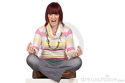 Angry young woman sitting cross-legged, isolated