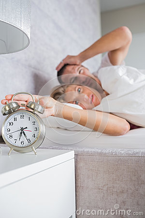 Annoyed couple looking at alarm clock in the morning with woman