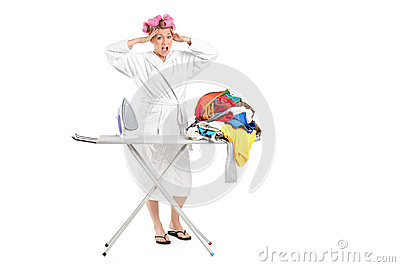 Annoyed housewife with ironing board and clothes