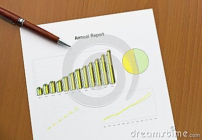 Annual report chart print, pen on desk.