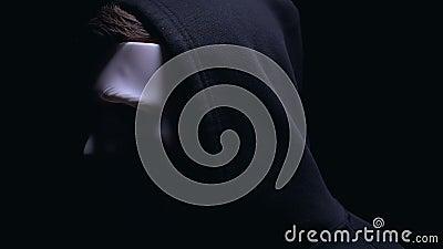 Anonimo incappucciato nel fronte di giro della maschera alla macchina fotografica, criminale irriconoscibile stock footage