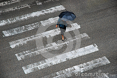 Anonymous woman with umbrella crossing street