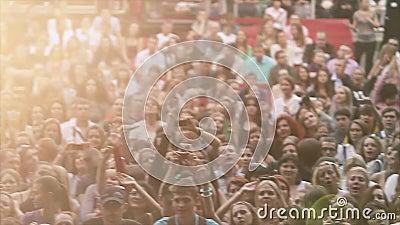 Ansicht von zujubelnden Leuten am Sommerlivekonzert Musikband, die am Stadium durchführt masse Sun-Strahlen stock video footage