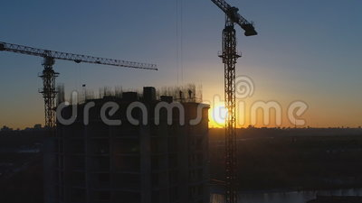 Antenne van bouwwerf met kranen en arbeiders bij zonsondergang wordt geschoten die stock footage