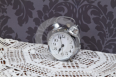 Antique alarm clock on table cloth