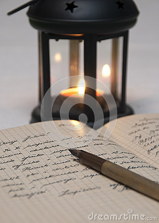 Antique black candlestick, candle and old letter