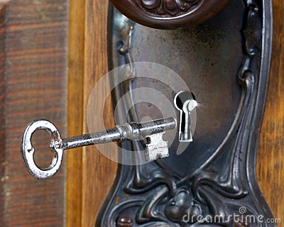 Antique door with skeleton key going into key hole