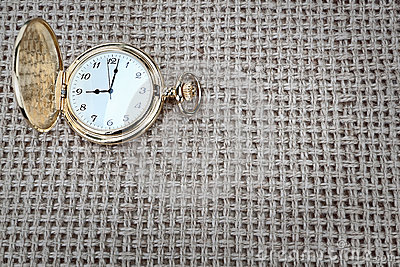 Antique pocket watch on a textured burlap.